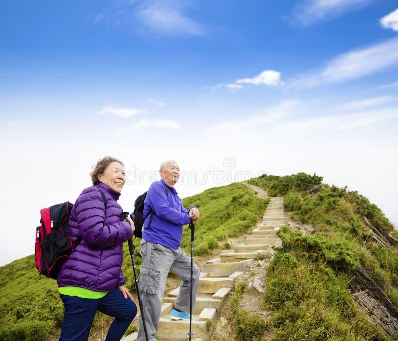 Lyckliga höga par som fotvandrar på berget arkivfoton