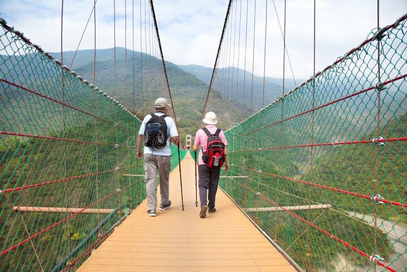 Lyckliga höga par som går på bron i net arkivfoto