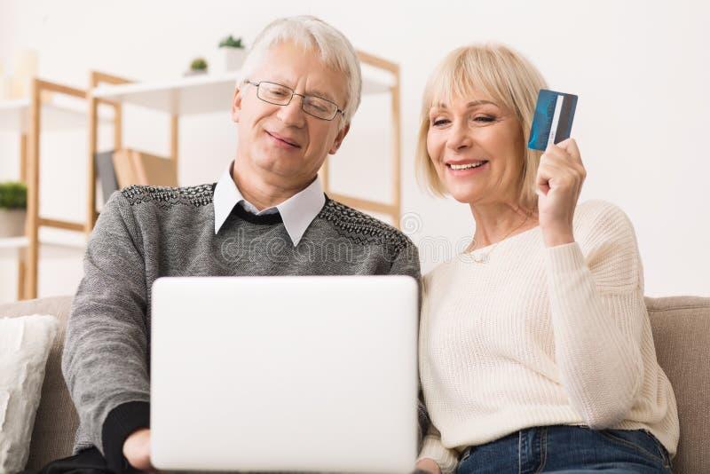 Lyckliga höga par som gör online-köp på bärbara datorn royaltyfri bild