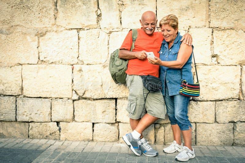 Lyckliga höga par som har gyckel med en modern smartphone arkivfoto