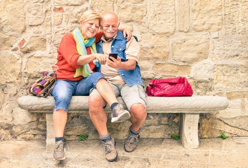 Lyckliga höga par som har gyckel samman med den smarta telefonen för mobil fotografering för bildbyråer