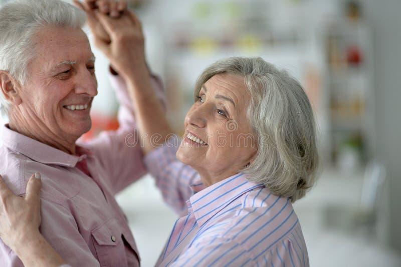 Lyckliga höga par som hemma dansar royaltyfria foton