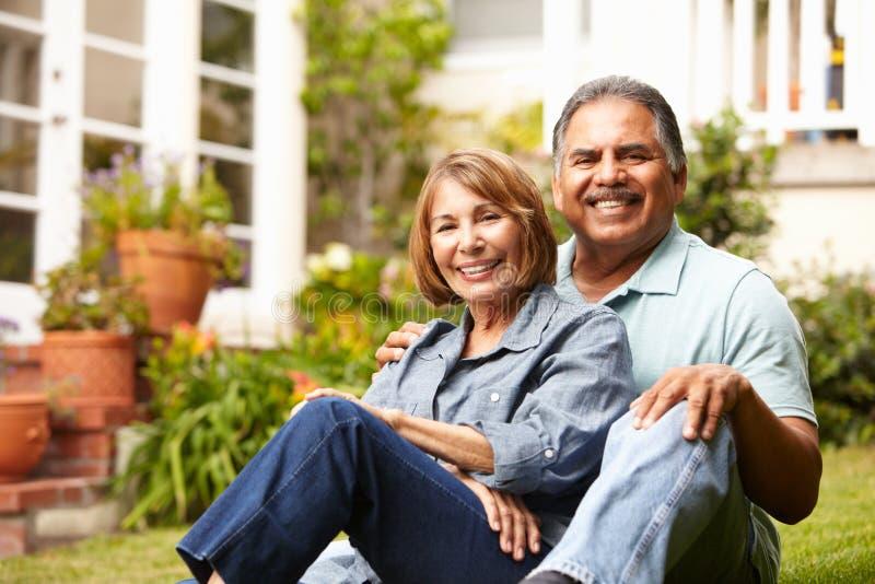 Lyckliga höga par som kopplar av i trädgård royaltyfri foto