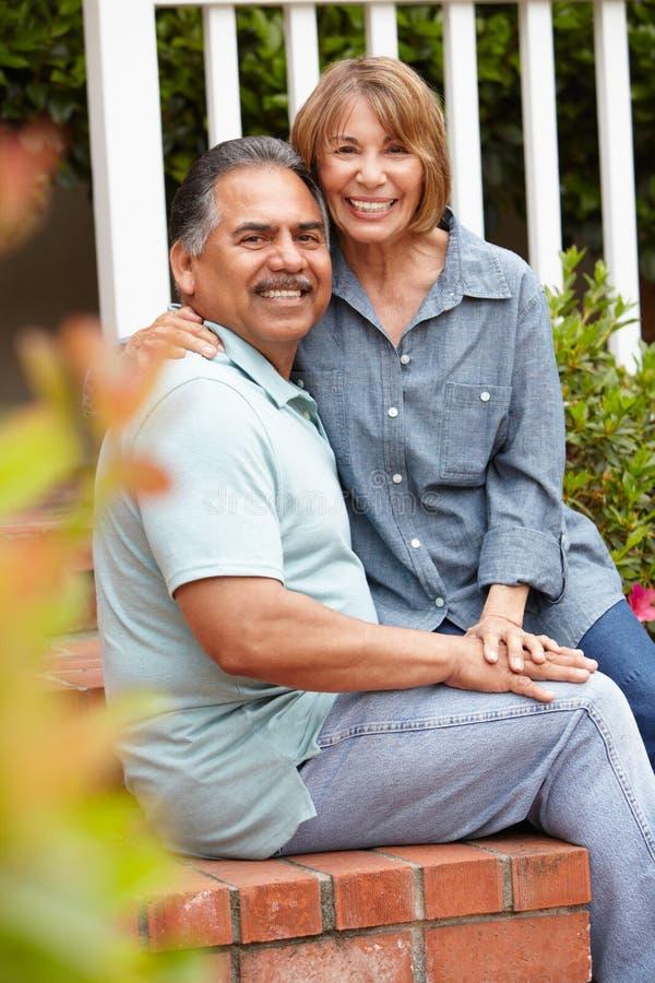 Lyckliga höga par som kopplar av i trädgård arkivfoto