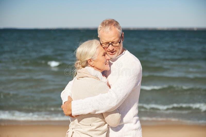 Lyckliga höga par som kramar på sommarstranden royaltyfri foto