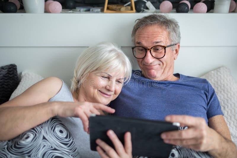 Lyckliga höga par som ligger i säng genom att använda minnestavlan arkivbilder