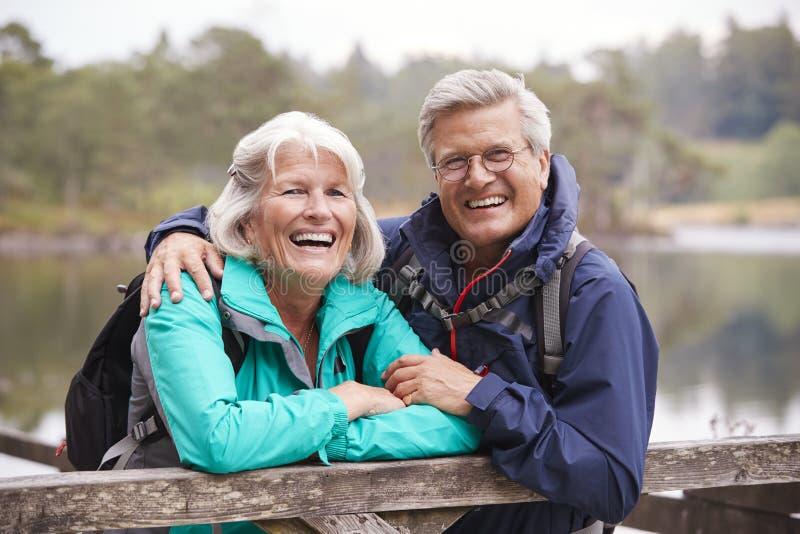 Lyckliga höga par som lutar på ett trästaket som skrattar till kameran, slut upp, sjöområde, UK arkivbilder
