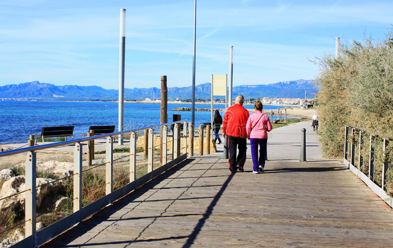 Lyckliga höga par som promenerar kusten mediteraneahavet royaltyfri bild