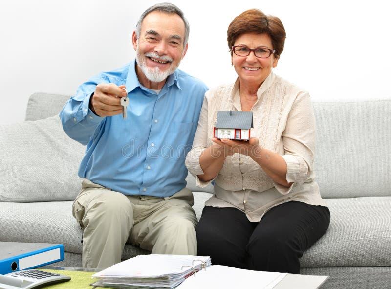 Lyckliga höga par som rymmer ett litet hus royaltyfri foto