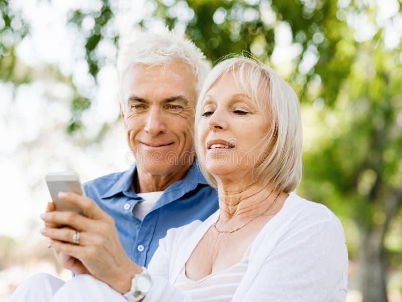 Download Lyckliga Höga Par Som Ser Smartphonen Fotografering för Bildbyråer - Bild av kläder, pensionärer: 78729077