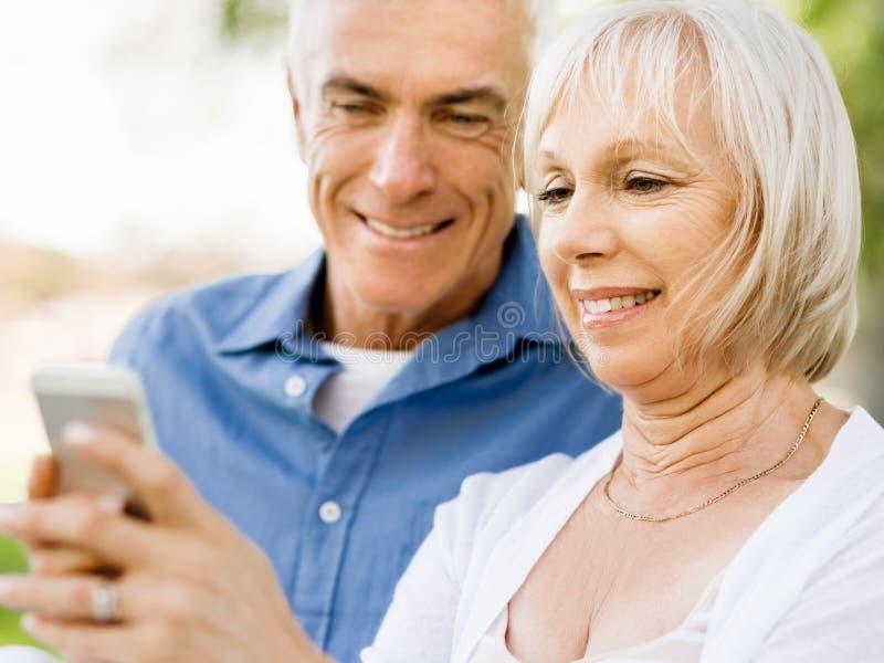 Download Lyckliga Höga Par Som Ser Smartphonen Arkivfoto - Bild av affektion, livstid: 78729510