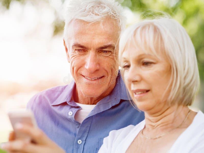 Download Lyckliga Höga Par Som Ser Smartphonen Arkivfoto - Bild av activatoren, shopping: 78730646