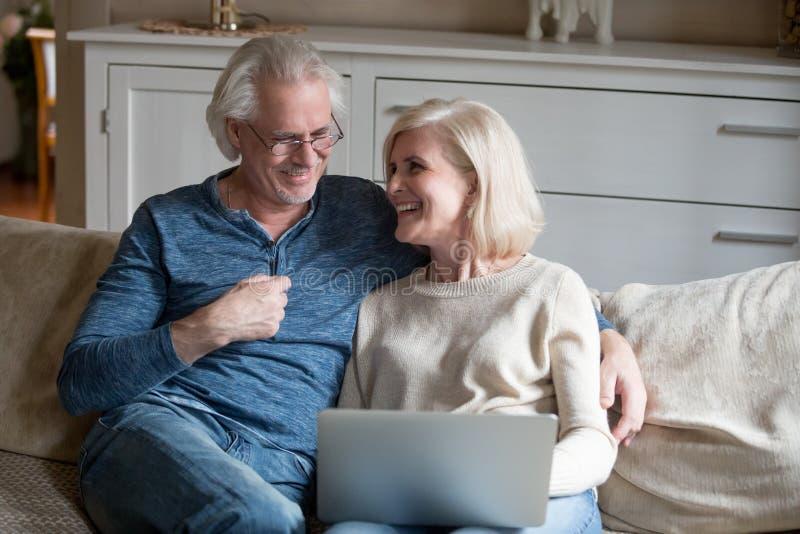 Lyckliga höga par som skrattar att koppla av med bärbara datorn i vardagsrum royaltyfri fotografi