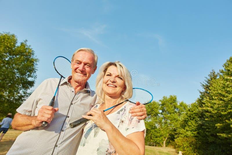 Lyckliga höga par som spelar badminton royaltyfri fotografi