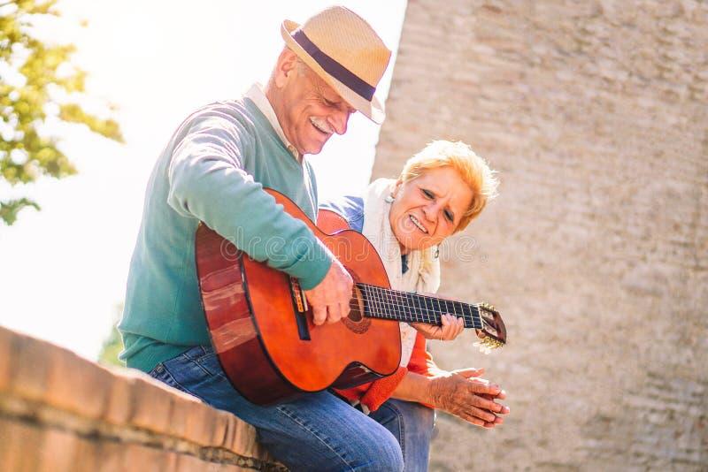 Lyckliga h?ga par som spelar en gitarr och har ett utomhus- romantiskt datum - moget folk som har gyckel som tillsammans tycker o arkivbilder