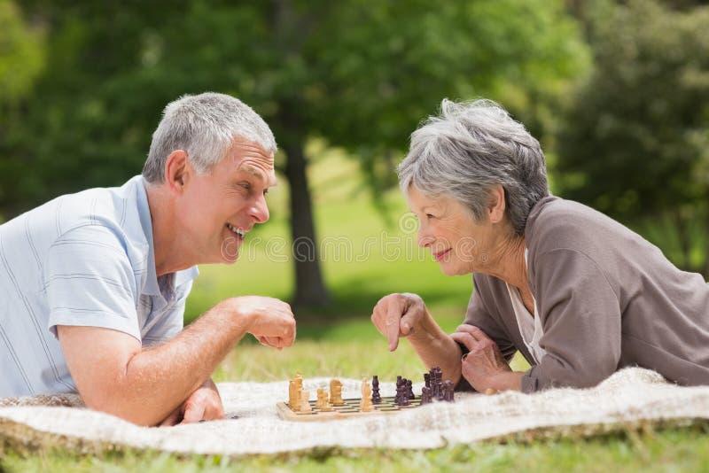 Lyckliga höga par som spelar schack på, parkerar royaltyfria bilder