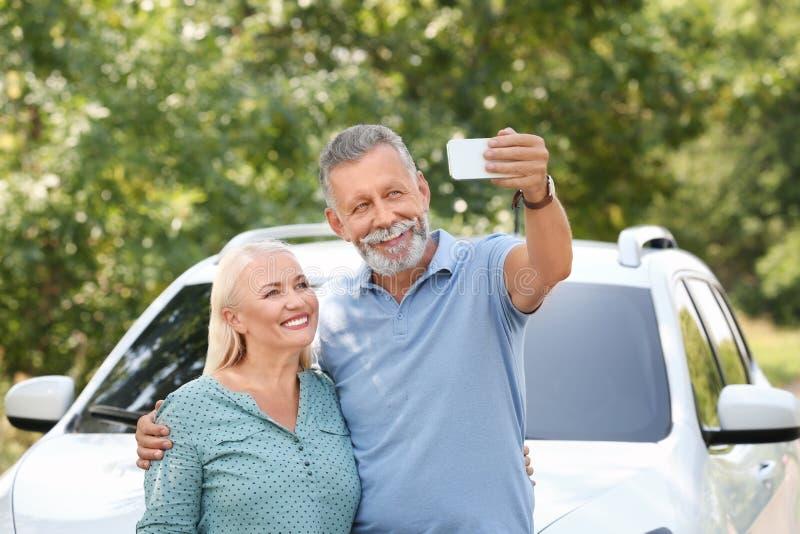Lyckliga höga par som tar selfie nära bilen arkivbild
