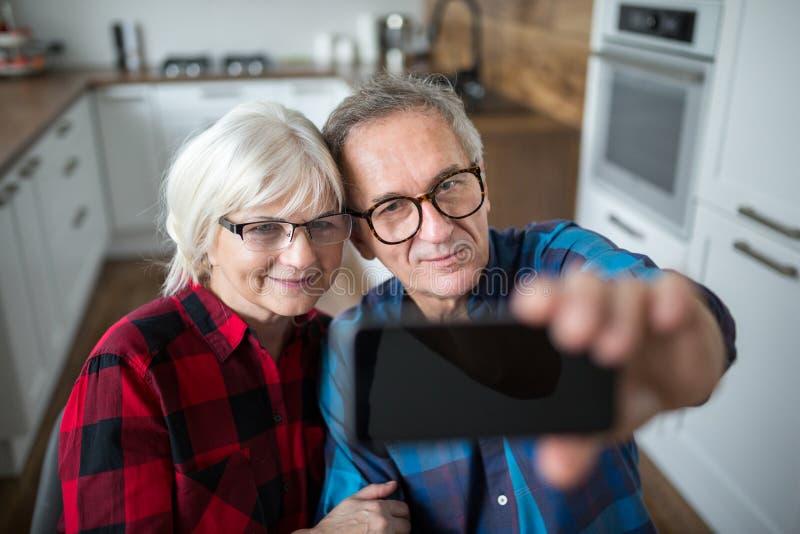 Lyckliga höga par som tar selfie vid smartphonen fotografering för bildbyråer