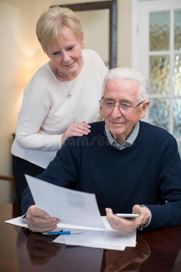 Lyckliga höga par som tillsammans granskar hemhjälpfinanser arkivbild
