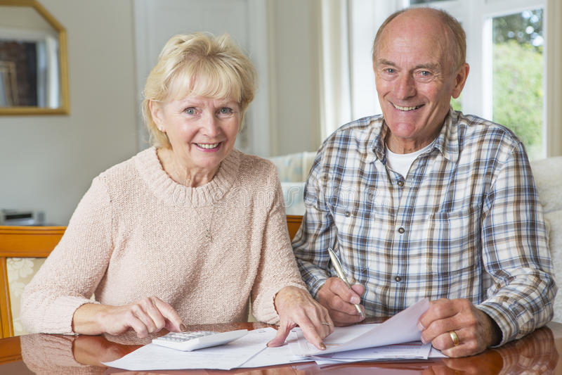 Lyckliga höga par som tillsammans granskar hemhjälpfinanser royaltyfri bild