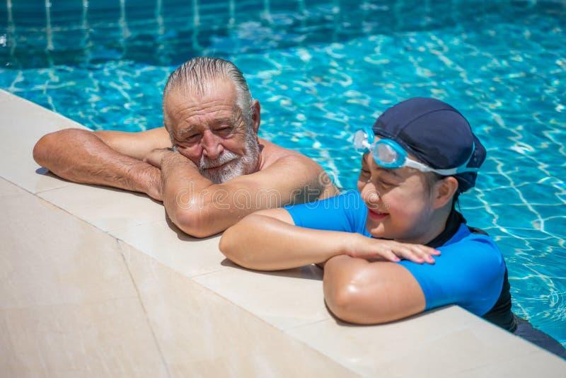 Lyckliga höga par som tillsammans kopplar av i simbassäng barnfadergyckel som har att leka tillsammans avgång genomkörare, kondit arkivfoton