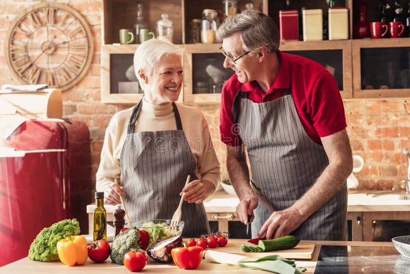 Lyckliga höga par som tillsammans lagar mat på kök royaltyfri bild