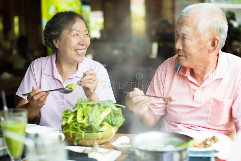 Lyckliga höga par som tycker om varma krukor arkivfoto