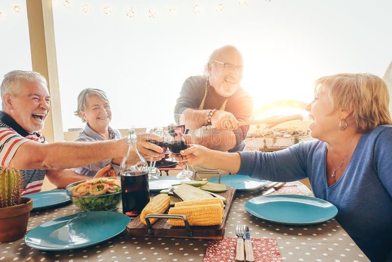 Lyckliga höga vänner som har gyckel som hurrar med rött vin på grillfesten i den utomhus- terrassen - äldre folk som äter middag  royaltyfria foton