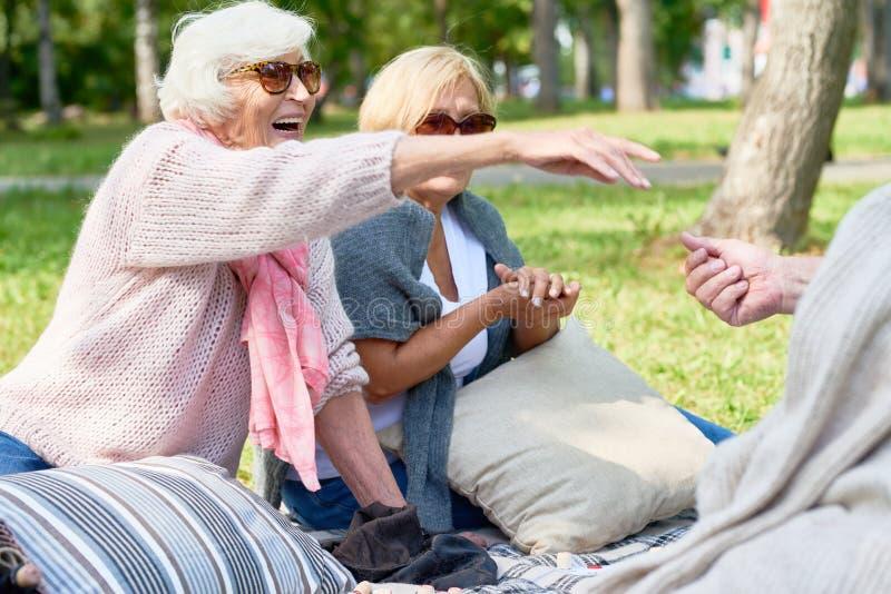 Lyckliga höga vänner som tycker om picknicken parkerar in royaltyfri foto