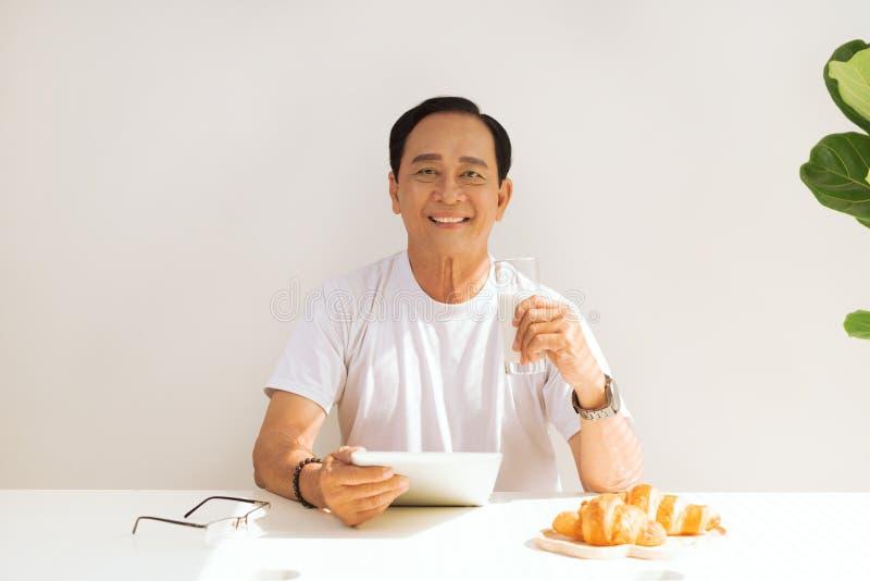 Lyckliga h?ga par som har den hemmastadda giffelfrukosten och dricker, mj?lkar och att trycka p? p? den digitala minnestavlan arkivbilder
