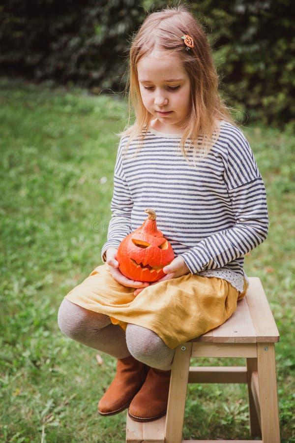 lyckliga halloween Härliga le litet barnplatser på trästol och liten pumpa för håll silar nolla-lyktor utomhus royaltyfria bilder