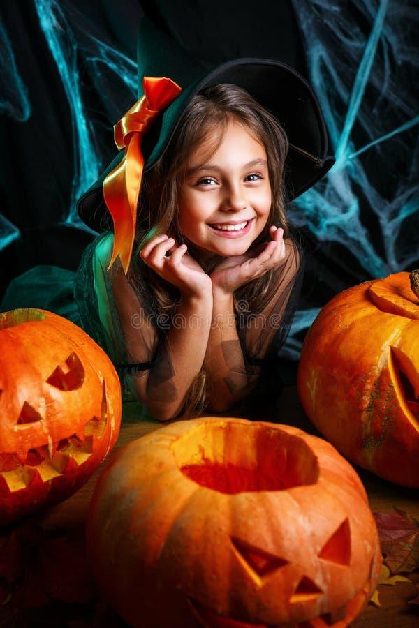 lyckliga halloween Nätt flicka för litet barn i häxadräkt med att snida pumpa Lycklig familj som förbereder sig för allhelgonaaft royaltyfri fotografi