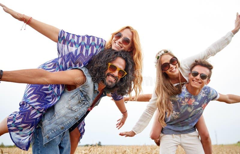 Lyckliga hippievänner som har gyckel på sädes- fält royaltyfria bilder