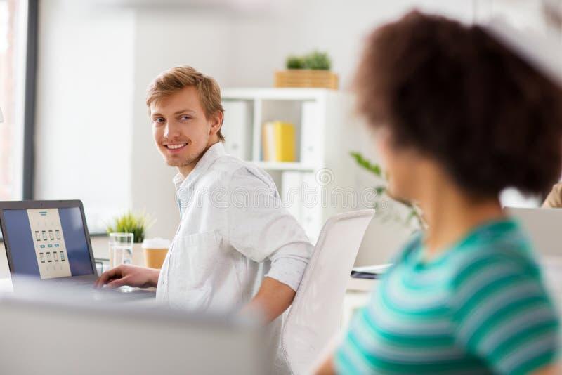 Lyckliga idérika arbetare med bärbara datorer på kontoret royaltyfri foto