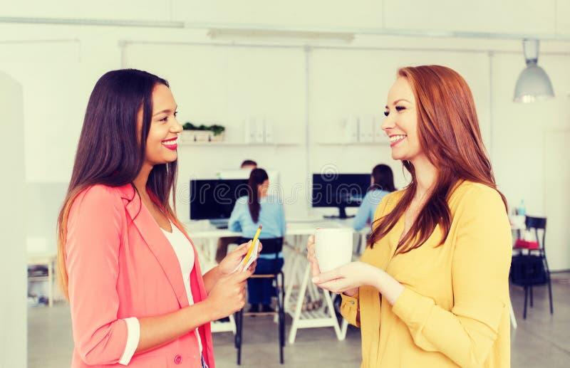 Lyckliga idérika kvinnor som talar på kontoret royaltyfri bild