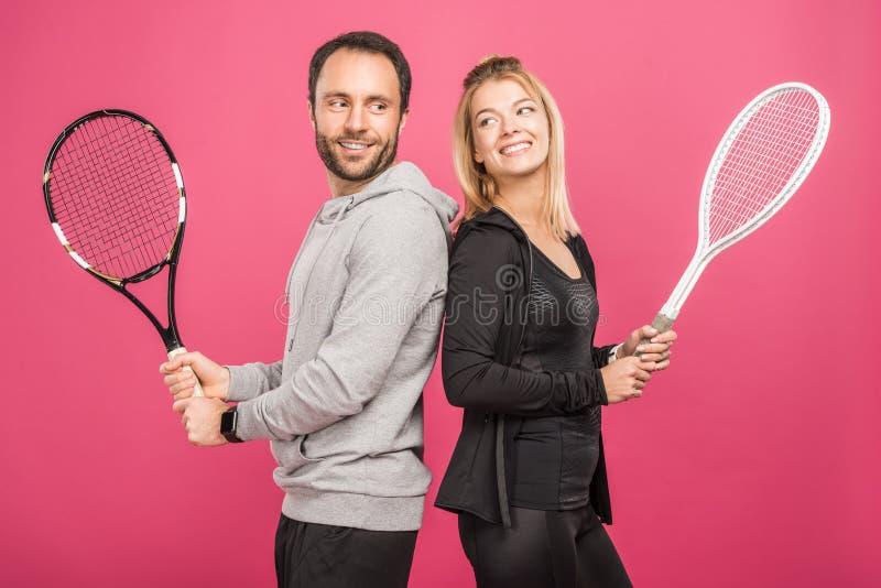 lyckliga idrotts- par som rymmer tennisracket som isoleras arkivbilder