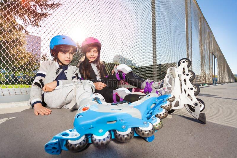Lyckliga inline-skateboradåkare som utomhus sitter på golvet arkivfoton