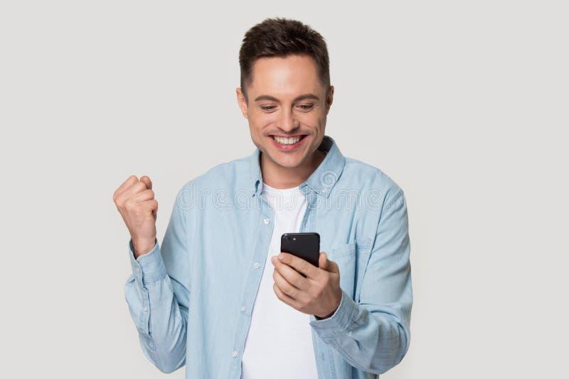 Lyckliga isolerade Caucasian spännande får det bra meddelandet på mobil arkivfoton