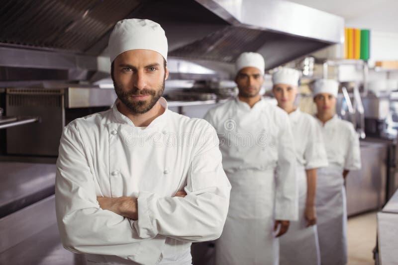 Lyckliga kockar team anseende tillsammans i kommersiellt kök royaltyfri foto