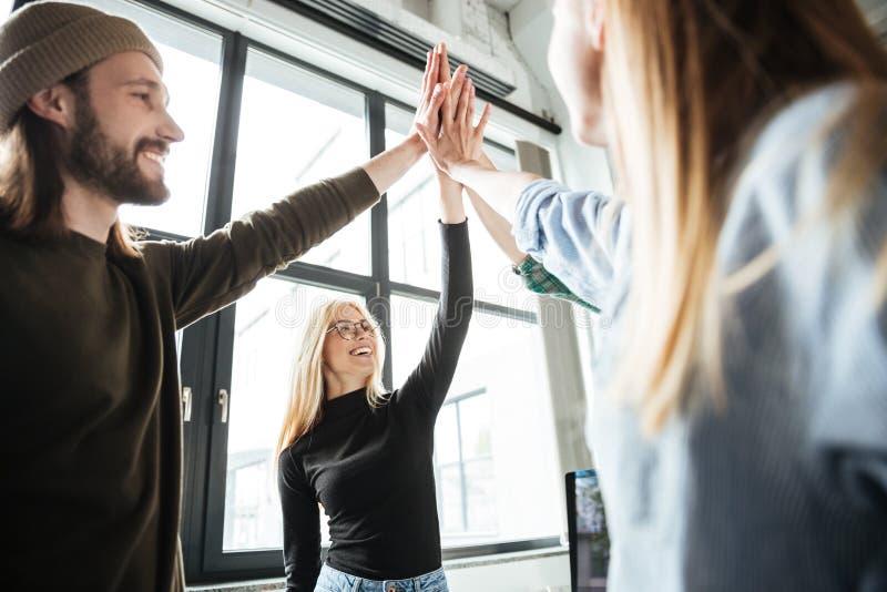 Lyckliga kollegor ger i regeringsställning höjdpunkt fem till varandra royaltyfri foto