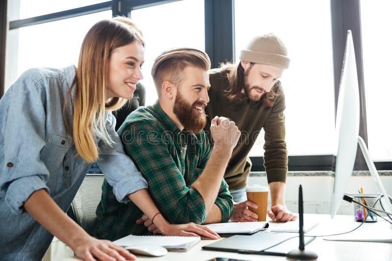 Lyckliga kollegor i regeringsställning som använder datoren royaltyfria foton