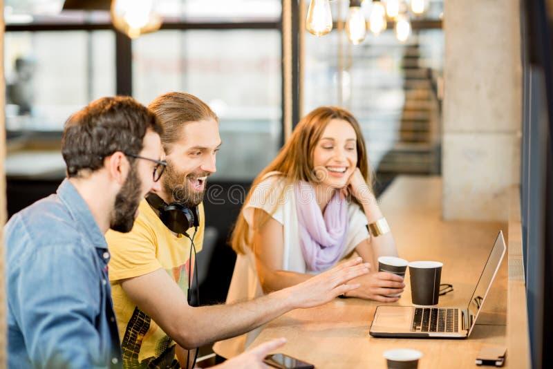 Lyckliga kollegor med bärbara datorn i kafét arkivfoto