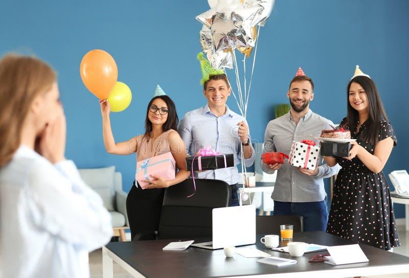 Lyckliga kollegor på överraskningpartiet för ung kvinna på hennes födelsedag i regeringsställning royaltyfri fotografi