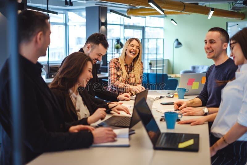 Lyckliga kollegor som skrattar i kontorsmötet royaltyfria bilder