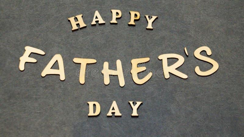 Lyckliga kombinationer för ord för dag för fader` som s göras av träbokstäver på en svart tabell Hälsningar för dag för fader` s arkivbild