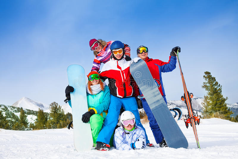 Lyckliga kompisar med snowboards och skidar royaltyfria bilder