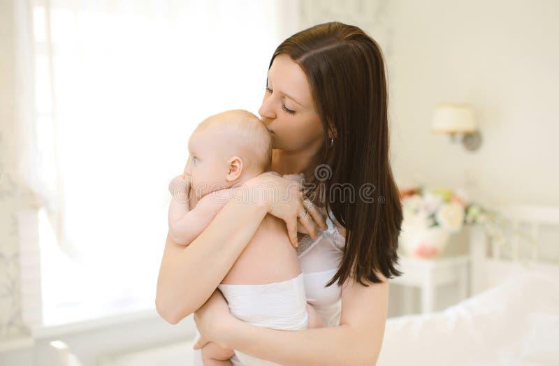 Lyckliga kramar för mamma försiktigt och att kyssa behandla som ett barn fotografering för bildbyråer