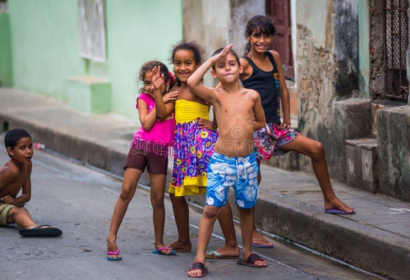 Lyckliga kubanska barn fångar ståenden i fattig färgrik kolonial gränd med leendeframsidan, i gammal havannacigarr, Kuban, Amerik arkivfoton