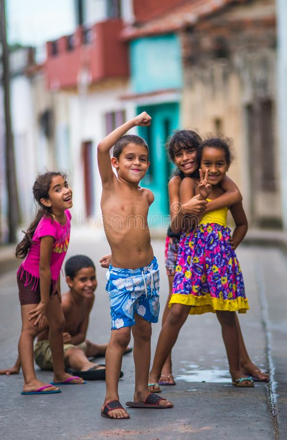 Lyckliga kubanska barn fångar ståenden i fattig färgrik kolonial gränd med optimistisk livstil, i gamla Habana, Kuban, Amerika royaltyfri foto