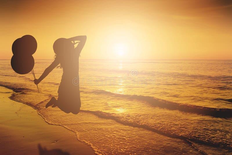 Lyckliga kvinnabanhoppning- och innehavballonger i havet sätter på land solnedgångsil royaltyfria foton